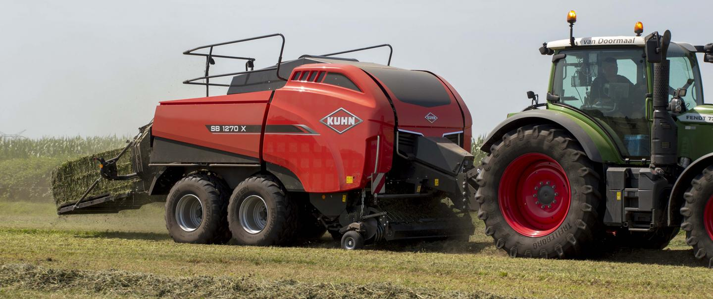 Large square baler baling in a straw field